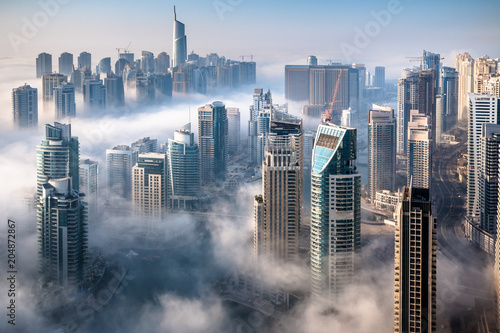 Zdjęcia na płótnie, fototapety na wymiar, obrazy na ścianę : Dubai skyline, an impressive aerial top view of the city in Dubai Marina on a foggy day