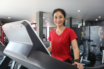 Asian women running sport shoes at the gym while a young caucasian woman is having jogging on the treadmill © tuiphotoengineer