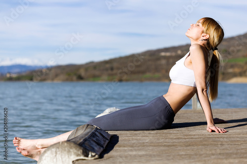 Wall mural Fit and sporty young woman relaxing after work out next to the lake.