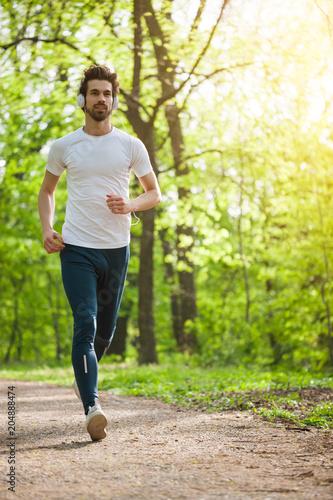 Fotobehang Hardlopen Young man is jogging in park. He is listening music on headphones.