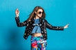 emotional stylish girl model in studio on a blue background, wearing bright leggings leather jacket sunglasses, dynamic pose, smile
