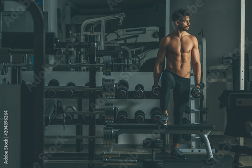 Fototapeta Strong and handsome young man doing exercise with dumbbells