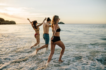 Friends holding hands and running at beach