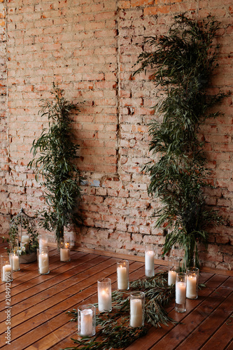 Fototapeta Loft interior with candles, brick wall, large window, living room in modern design