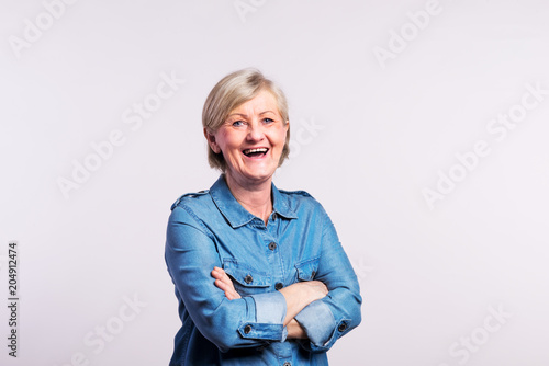 Foto Murales Portrait of a happy senior woman in studio, on a white background.