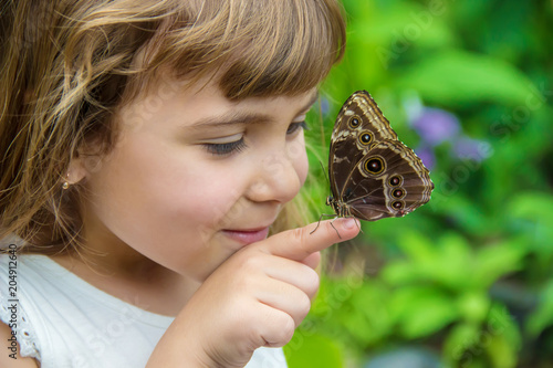 Fototapeta Child with a butterfly. Selective focus.