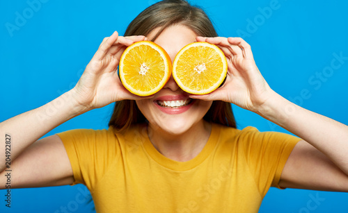 Cheerful girl holding two slices orange in front of eyes.