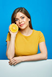 Woman holding orange fruit with blank banner