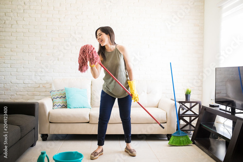 Fototapeta Funny woman using mop as microphone and singing