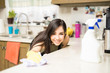 Focused woman cleaning stains in kitchen counter