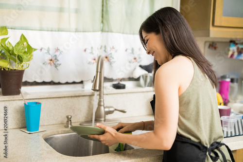 Side view of woman washing utensils