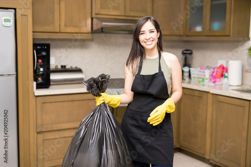 Happy young housewife holding disposal bag with trash