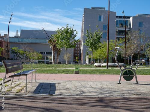 Banco en el parque junto a bicicleta  estática.