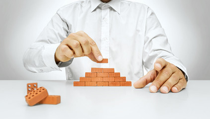 Concept of building and construction, hand put the last brick on the wall -Businessman hand placing a brick on a wall