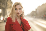 Beautiful woman walking in the street, wearing a red trench coat