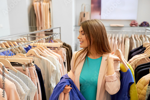 shopping, fashion, sale and people concept - happy young woman with clothes on hangers in mall or clothing store