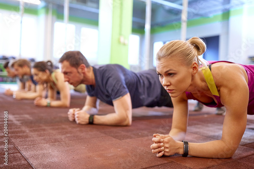 Wall mural fitness, sport, exercising and people concept - woman with heart-rate tracker at group training doing plank exercise in gym