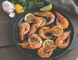 fried roasted shrimps in frying pan with lemon greens parsley garlic - 204949228