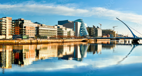 Modern buildings and offices on Liffey river in Dublin on a bright sunny day - 204951241