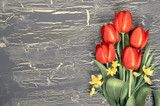 Bunch of red tulips and lily of the valley flowers on rustic background, space