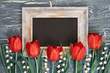 Blackboard and bunch of red tulips and lily of the valley flowers on rustic background, space