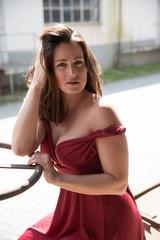 erotische junge Frau in langen roten Kleid auf altem Fabrikgelände