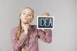 Thinking woman holding idea sign