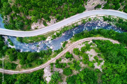 Fotobehang Groene Aerial view over mountain road and curves going through forest landscape