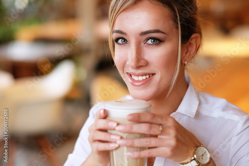 Poster Smiling woman in a good mood with cup of coffee sitting in cafe.