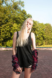 Gorgeous blonde model with long hair wearing casual clothes and posing in the park