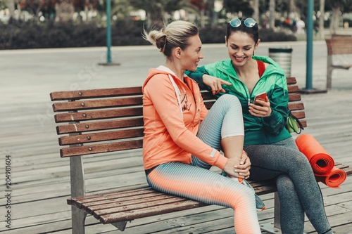 Poster Happy two girls are talking and laughing while sitting on bench outdoor. Lady is showing smartphone to her friend. They are wearing sportswear