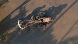 Man operating a cultivator machine in the paddy field drone footage from above - 205011448