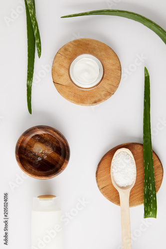 Plakat top view of organic cream in container and spoon with salt on wooden slices, aloe vera leaves and wooden bowl with aloe vera juice