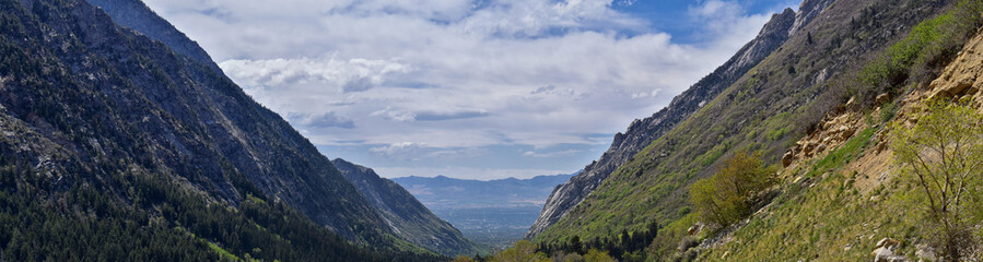 Panoramic Views of Wasatch Front Rocky Mountains from Little Cottonwood Canyon looking towards the Great Salt Lake Valley in early spring with melting snow, pine trees and budding Quaking Aspen in Uta © Jeremy