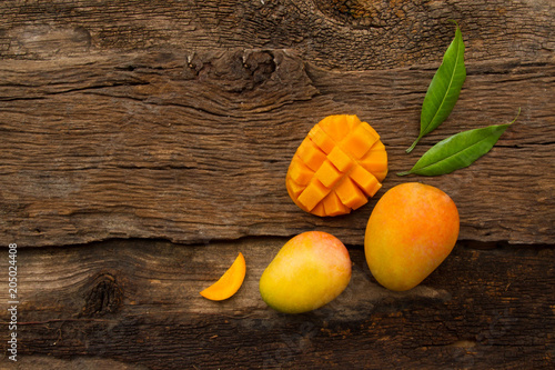 Mango fruit with slice cut and leaf on wooden background, top view. tropical fruits mango on wooden background - 205024408