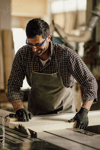 Skilled carpenter cutting a piece of wood in his woodwork workshop