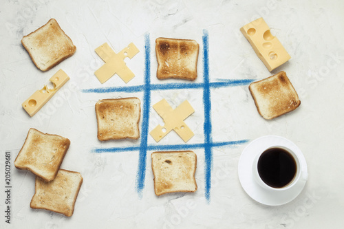 Noughts and Crosses Choice Game Competition of Crosses from Cheese and Square Toasted Toast, Cup with Black Coffee, Cheese  White Stone Background