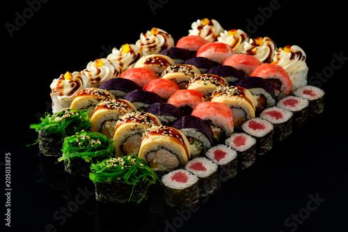 Plexiglas Sushi bar Fresh Sushi rolls set served on black background. Japanese seafood sushi