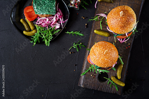 Big sandwich - hamburger burger with beef,  tomato, basil cheese and arugula. Top view. Flat lay - 205039670