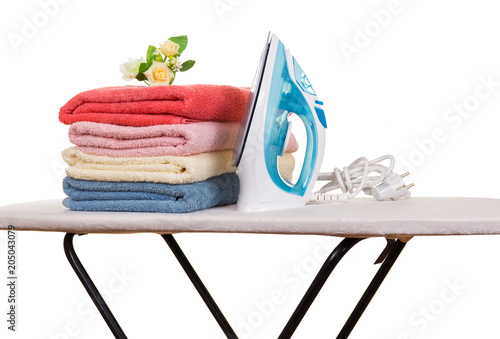 Electric iron and stack of clean towels on Ironing Board isolated on white