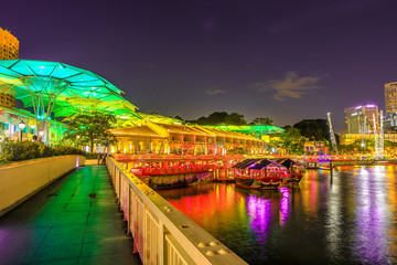 Clarke Quay bridge and Riverside area at evening in Singapore, Southeast Asia. Waterfront skyline reflected on Singapore River. Popular attraction for nightlife.