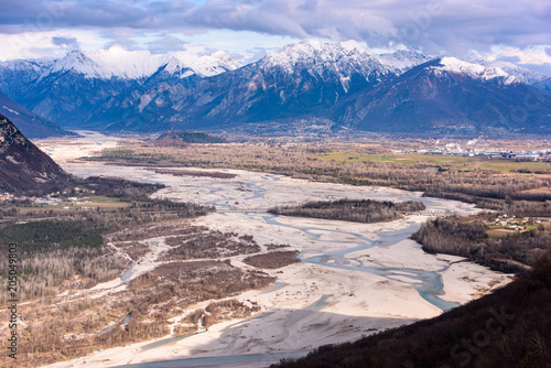 Fotobehang Blauwe hemel The slow flow of the Tagliamento river cradled by its mountains.