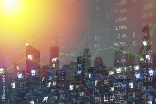 Cityscape with lighted windows at night and stock market chart.