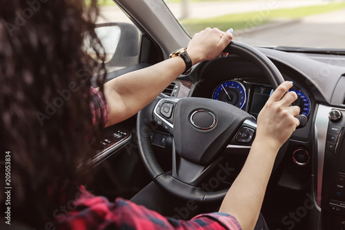 Wall mural  Brunette lady is holding her hands behind wheel of car.