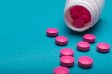 Medication bottle and bright pink pills spilled on dark blue coloured background. Medication and prescription pills close up background.