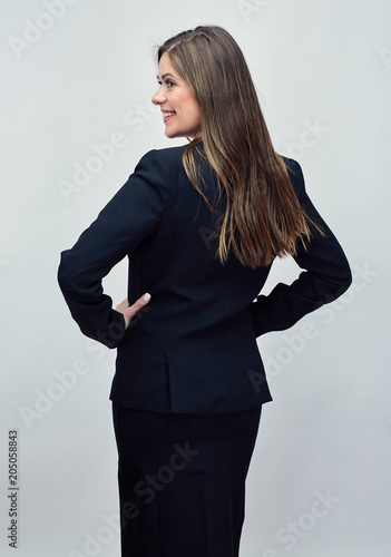 Smiling woman in business suit standing back.