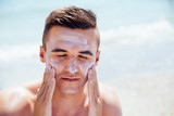 Attractive man putting tanning cream on his face, closing his eyes, takes a sunbath on the beach. Healthcare. - 205072687