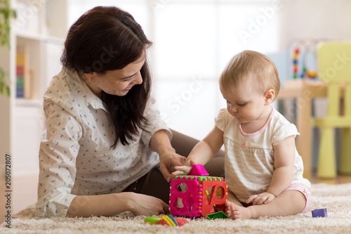 Babysitter looking after baby. Child girl plays with sorter toy sitting on the carpet at home © Oksana Kuzmina