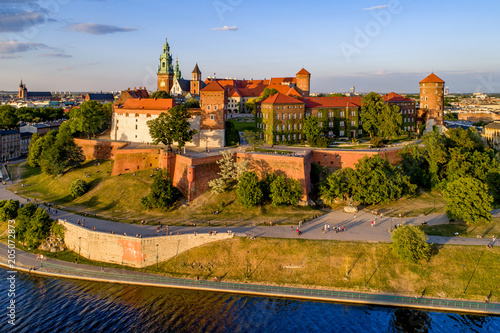 Aluminium Krakau Krakow, Poland. Wawel Hill, royal Cathedral and castle. Aerial view in sunset light. Vistula River and far view of St. Mary (Mariacki) church on the left. Riverbank with promenade and walking people