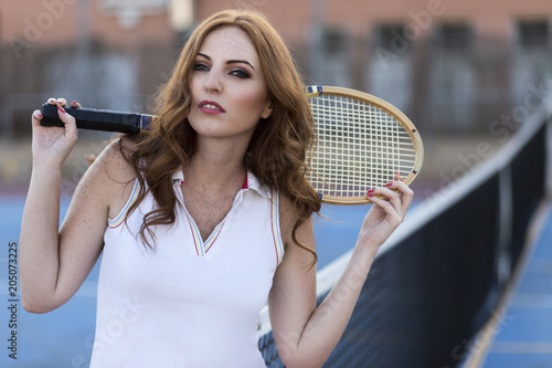Plexiglas Tennis .Redhead girl on tennis court with old racket